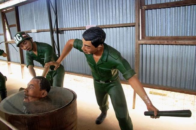 chúng tống tù nhân vào thùng phuy đầy nước