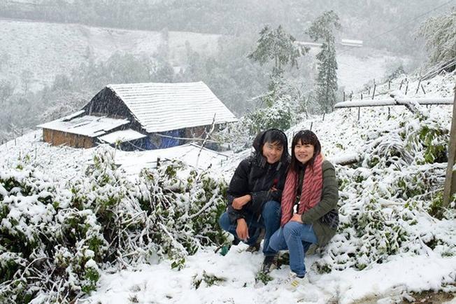 Du khách thích thú chụp ảnh bên những bông tuyết trắng ở Sa Pa