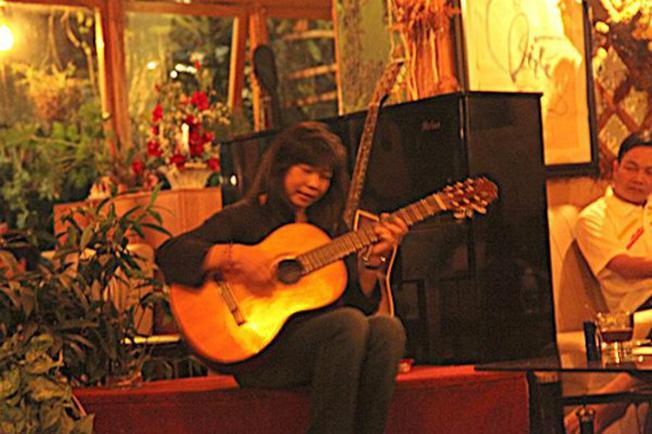 Hình ảnh cô chủ quán ngồi hát trên sân khấu