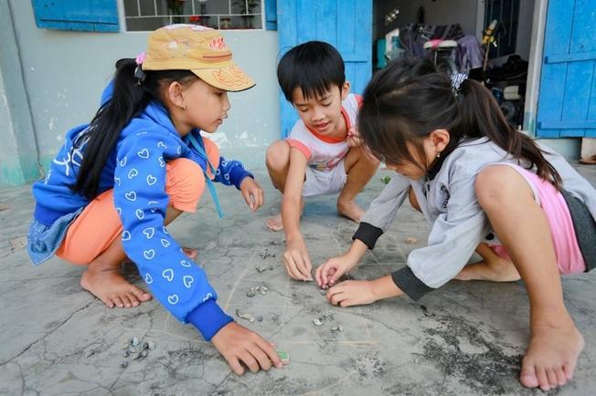 Các em nhỏ say sưa trong trò chơi ô ăn quan