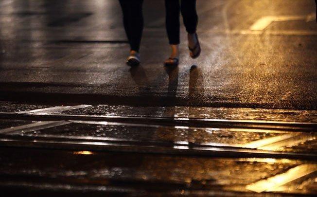 Mặt đường loáng nước dưới ánh đèn.