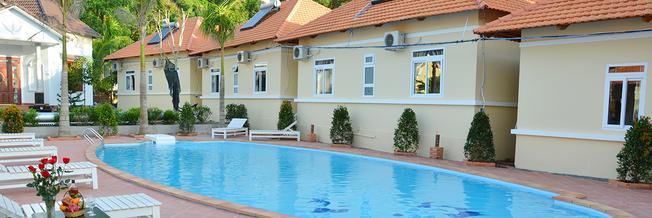 Bể bơi xanh và có các băng ghế dài để thư gian